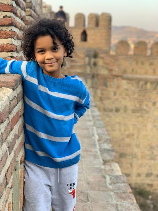 Mixed race boy on the castle wall at Narikala Fortress in Tbilisi, Georgia